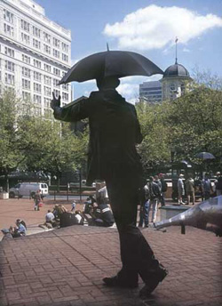 "The ""commuter with umbrella"" statue stands at Pioneer Courthouse Square downtown."